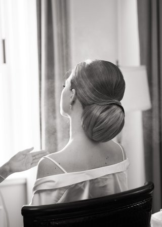 black-and-white-photo-of-bride-getting-ready-wedding-in-robe-off-shoulder-with-updo-coiffure-elegant