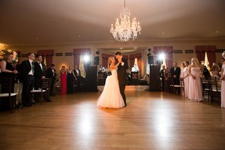 bride-and-groom-on-wood-dance-floor-under-chandelier