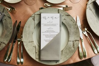 wedding-menu-with-modern-calligraphy-salad-entree-choices-in-grey-napkin-on-wood-table