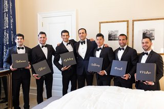 groom-and-groomsmen-in-tuxedos-bow-ties-holding-boxes-personalized-with-their-names-on-them-in-gold