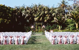 white-ceremony-chairs-greenery-arch-two-flower-arrangements-pink-chair-covers-on-back-row