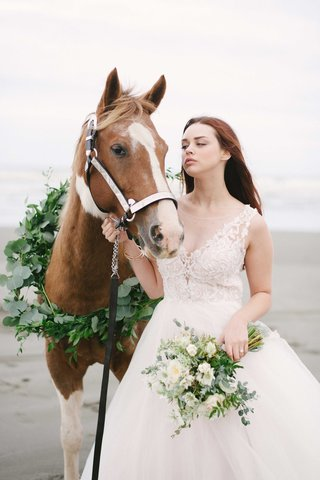 bride-leads-a-horse-with-a-green-wreath-made-of-foliage-on-a-beach-with-her-bouquet