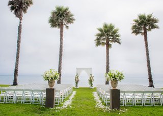 wedding-ceremony-on-grass-lawn-overlooking-beach-ocean-palm-trees-lily-flowers-in-stone-urn-drapery