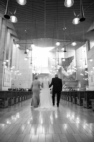 black-and-white-photo-of-parents-walking-bride-down-the-aisle-at-cathedral-of-our-lady-of-the-angels