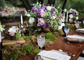 outdoor-wedding-reception-with-wood-table-moss-runner-urn-with-white-purple-and-green-flowers