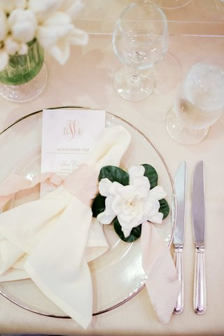 wedding-place-setting-with-clear-charger-place-cream-napkin-tied-with-blush-gardenia-bloom-on-side