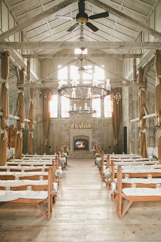 wedding-ceremony-with-benches-white-cushions-fireplace-medieval-chandeliers-wood-beams-ceiling-fans