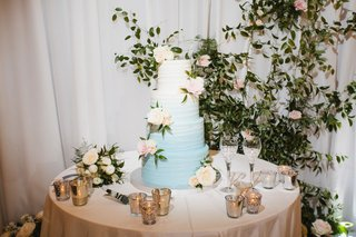wedding-cake-on-table-next-to-sweetheart-table-greenery-drapery-light-blue-to-white-ombre-colors