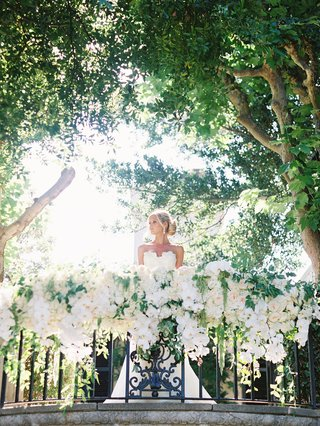 bride-in-white-wedding-gown-standing-on-alfresco-balcony-covered-in-greenery-cascading-white-orchids