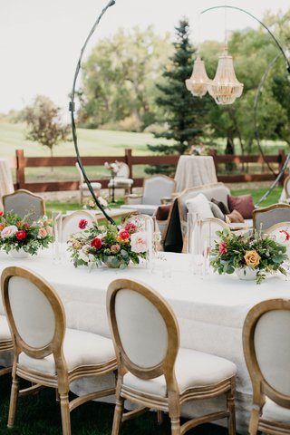 wedding-reception-stand-up-chandelier-white-table-french-upholster-chairs-pink-centerpiece-greenery