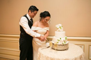 newlyweds-cutting-cake-together-three-tiered-white-flowers-circle-table