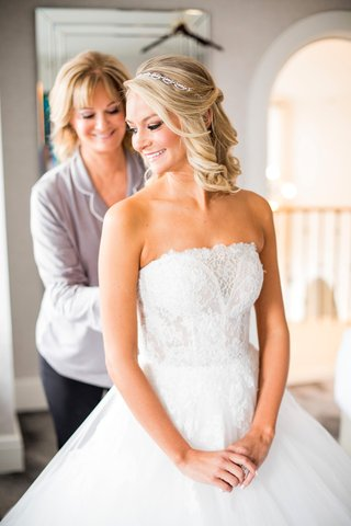 mother-of-the-bride-helps-bride-into-strapless-monique-lhullier-ball-gown