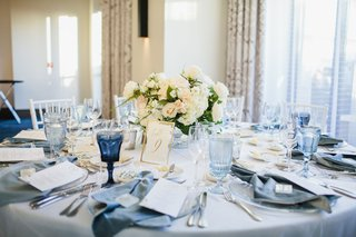 wedding-reception-ballroom-round-table-low-centerpiece-ivory-flowers-blue-glassware-velvet-napkin