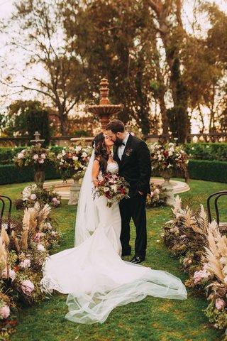 fall-wedding-stephanie-perez-and-brandon-hampton-kissing-custom-gown-greystone-mansion-aisle-whispy