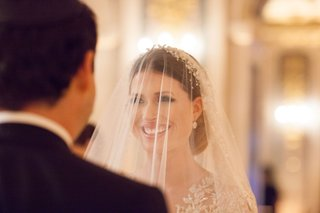 bride-looking-into-grooms-eyes-during-wedding-ceremony-long-sleeve-dress-with-illusion-details-veil