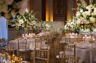 wedding-reception-flower-wall-round-tables-gold-chairs-tall-centerpiece-high-flowers-white-greenery