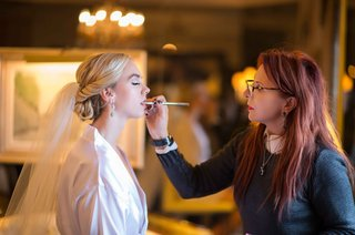 bride-with-blonde-hairstyle-getting-lips-done-by-makeup-artist