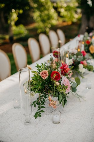 wedding-reception-long-table-taper-candle-pink-red-ranunculus-greenery-outdoor-wedding-reception
