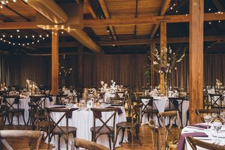 rustic-wedding-reception-round-tables-with-wood-chairs-and-wood-beams-ceilings-floors-purple