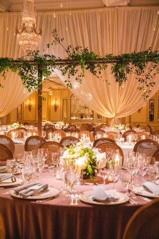 wedding-reception-drapery-chandelier-greenery-round-table-lavender-linen-low-centerpiece-green
