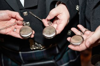 groom-groomsmen-in-black-blazers-show-metal-pocket-watches-with-monograms-in-green