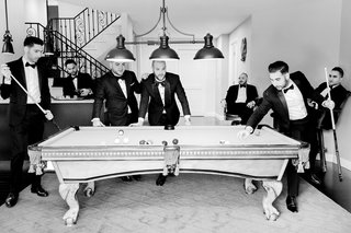 black-and-white-photo-of-groom-and-groomsmen-playing-pool-before-wedding