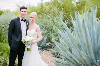 bride-and-groom-stand-in-arizona-desert-with-white-bouquet