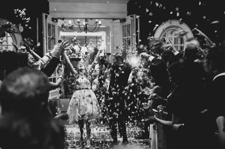 black-and-white-photo-of-grand-exit-with-flower-petals-thrown-over-newlyweds