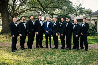 groom-in-navy-blue-tuxedo-boutonniere-with-groomsmen-in-regular-black-white-tuxedos-on-grass-lawn