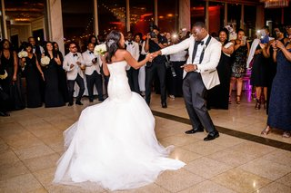 bride-in-strapless-wedding-dress-dancing-with-groom-in-white-tuxedo-jacket-at-wedding-reception