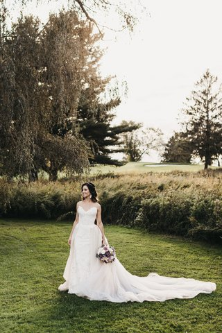 bride-in-nicole-spose-wedding-dress-with-long-train-standing-in-a-green-field