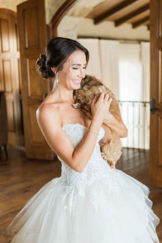 bride-in-strapless-monique-lhuillier-lace-wedding-dress-ball-gown-holding-small-tan-brown-dog