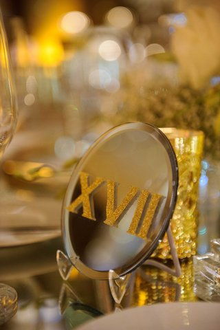 a-glittered-gold-table-number-in-roman-numerals-on-a-reflective-surface-mirror-table-number