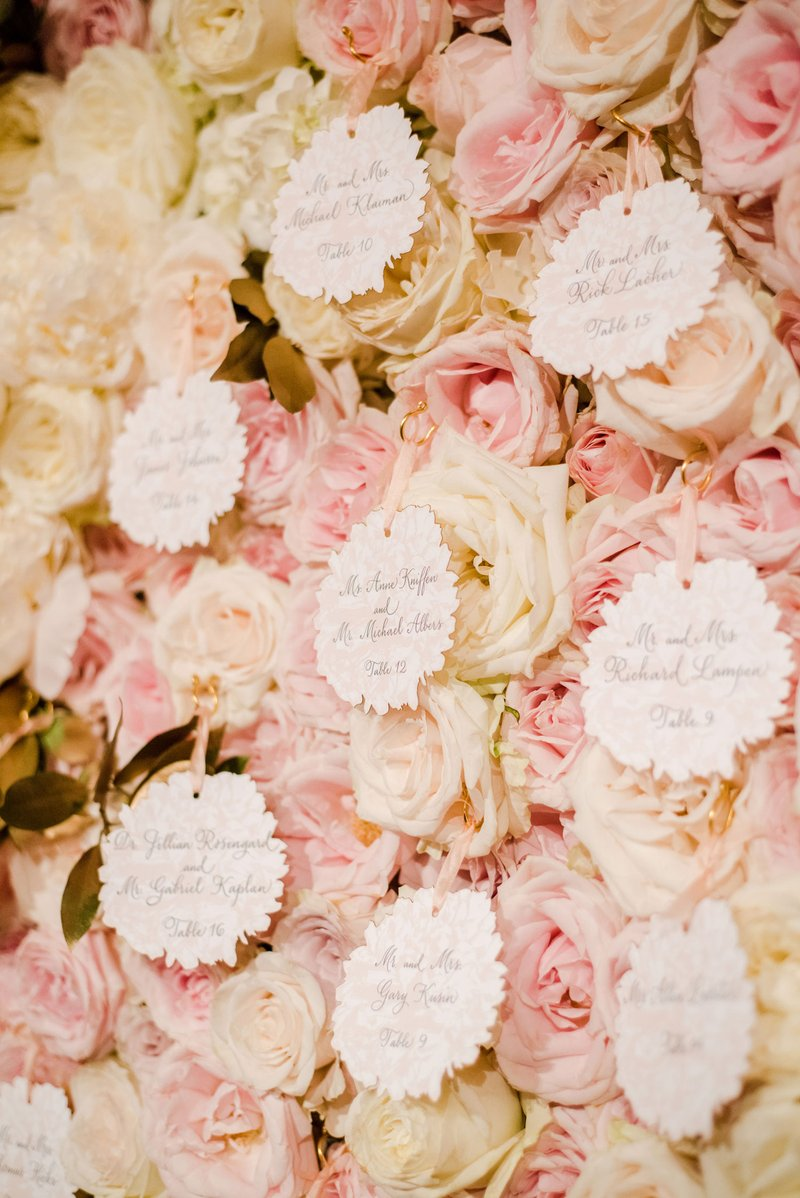 Escort Cards on White & Pink Flower Wall