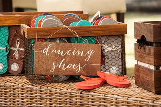 wedding-reception-flip-flops-in-crate-with-dancing-shoes-calligraphy-wooden-sign-at-outdoor-receptio