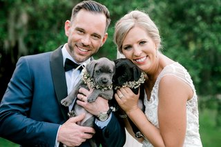 groom-in-navy-blue-tuxedo-jacket-bride-and-beaded-wedding-dress-with-cute-puppies-dogs-with-flowers