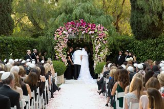wedding-ceremony-at-the-beverly-hills-hotel-groom-in-white-jacket-pink-white-green-wedding-arch