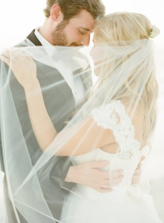 bride-in-a-monique-lhuillier-gown-with-a-lace-bodice-and-veil-embraces-groom-in-a-black-tuxedo