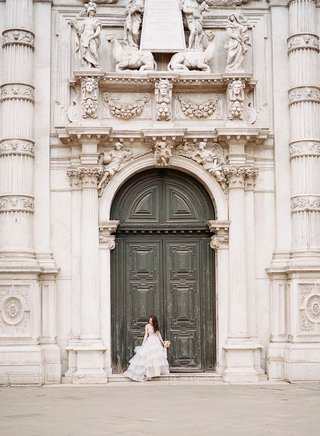 bride-in-hayley-paige-wedding-dress-in-front-of-historic-building-door-columns-carvings-sculpture