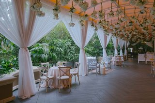 pink-drapery-at-outdoor-cocktail-hour-with-hydrangea-bundles-hanging-from-ceiling