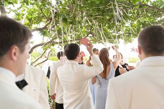 guests-grabbing-escort-cards-in-shapes-of-sea-shells-hanging-from-tree-cocktail-hour