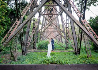 wedding-photo-portrait-under-bridge-navy-blue-suit-white-dress-santa-barbara-california-forest-venue