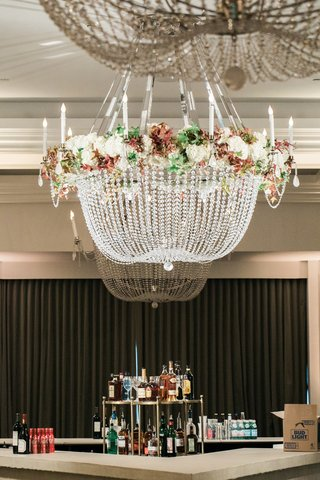 crystal-chandelier-with-floral-accents-suspended-over-the-bar-at-reception-for-50th-anniversary