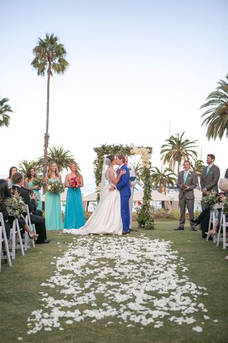 newlywed-couple-kiss-at-beach-wedding-with-palm-trees-in-back