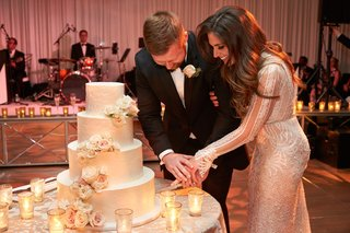 bride-in-inbal-dror-wedding-dress-and-groom-in-tuxedo-cutting-four-layer-ivory-wedding-cake-flowers