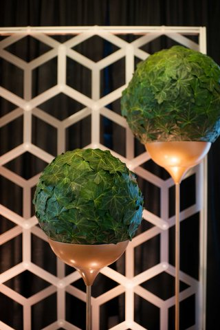 spherical-arrangements-of-foliage-resting-in-long-copper-stands-in-front-of-geometric-backdrop