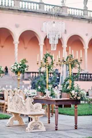 chandelier-suspended-over-opulent-ornate-sweetheart-table-with-carved-bench