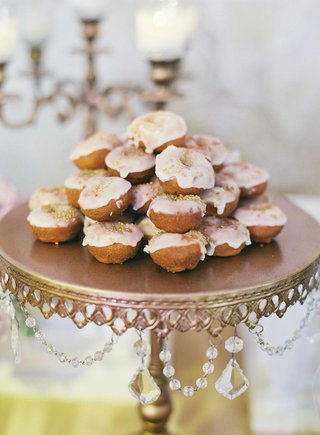 vintage-cake-stand-with-crystal-detail-holding-mini-doughnuts-with-white-frosting-and-gold-sprinkles