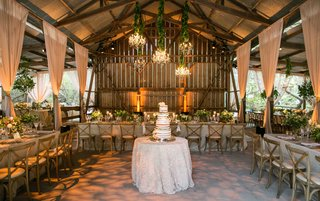 naked-cake-in-center-of-barn-open-side-venue-with-drapery-chandeliers-wood-beams-wood-chairs-long