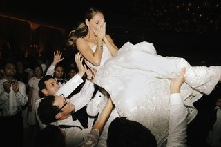 bride-in-naeem-khan-wedding-dress-ponytail-being-lifted-by-groom-and-friends-on-dance-floor